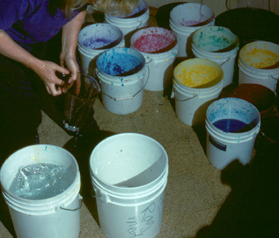 Five gallon buckets full of colorful pulp.